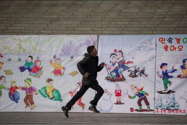 Một thiếu niên Triều Tiên chạy qua bức tường vẽ các trò chơi dành cho trẻ em tại lễ hội mừng năm mới ở Quảng trường Kim Nhật Thành tại Bình Nhưỡng. (Ảnh: AFP)