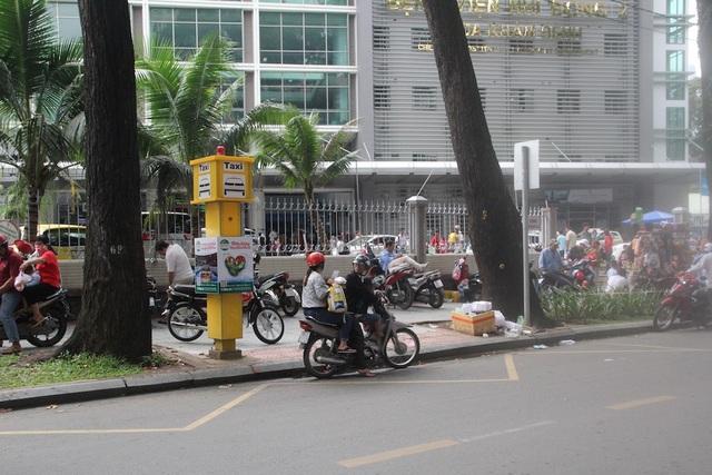 Điểm đón taxi có trụ báo taxi màu vàng và phần vạch kẻ cho phép dừng xe 2 phút