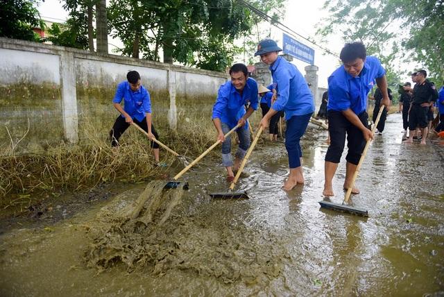 Cùng với lực lượng cảnh sát cơ động và PCCC, lục lượng thanh niên tình nguyện trên địa bàn xã cũng tham gia giúp người dân dọn vệ sinh.