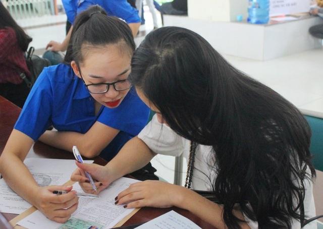 Nhiều thí sinh trúng tuyển đến sớm và được các tình nguyện viên hướng dẫn làm thủ tục nhập học