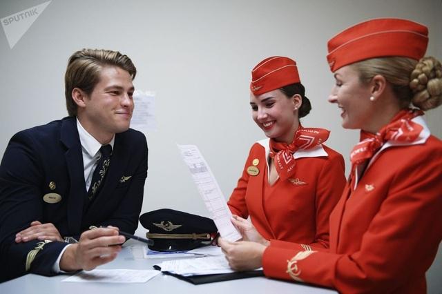 Tiếp viên hàng không nastasia Belousova và Nikita Duka trong một buổi họp cùng tiếp viên hàng không trưởng Maria Trofimova trước giờ bay.