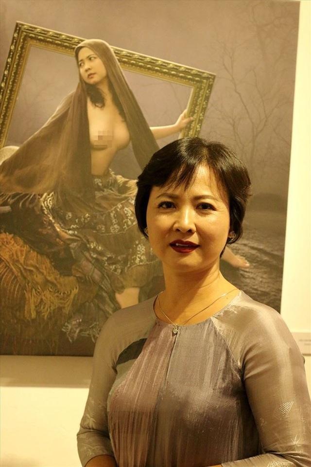 Bà Mộng Hà - vợ của nhiếp ảnh gia Dương Quốc Định bên bức ảnh do chồng mình thực hiện năm bà 37 tuổi trong triển lãm ảnh nude nghệ thuật tại Hà Nội vừa qua. Ảnh: TL.