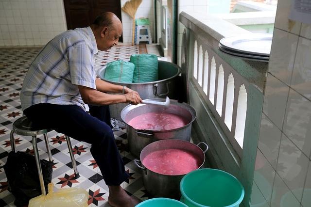 Người đàn ông nấu đồ ăn để phục vụ tín đồ đến hành lễ.