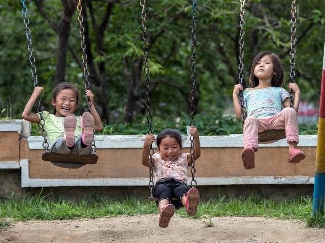 Nụ cười hồn nhiên của 3 em bé người Triều Tiên đang chơi xích đu ở Wonsan.