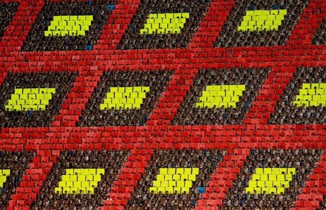 """Khoảng 17.490 trẻ em Triều Tiên đã ngồi trên các hàng ghế của sân vận động, sử dụng những cuốn sách lớn với các trang sách đổi màu để ghép thành những bức tranh khổng lồ hoặc những khẩu hiệu như """"Chúng ta có thể chiến thắng nếu bảo vệ thành công chủ nghĩa xã hội"""" hay """"Tổ quốc của chúng ta hùng mạnh nhất nhờ lãnh tụ tối cao""""."""