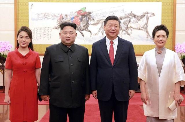 Đệ nhất phu nhân Triều Tiên Ri Sol-ju nắm tay nhà lãnh đạo Kim Jong-un khi chụp ảnh chung cùng Chủ tịch Trung Quốc Tập Cận Bình và phu nhân Bành Lệ Viện tại Bắc Kinh (Ảnh: Dailymail)