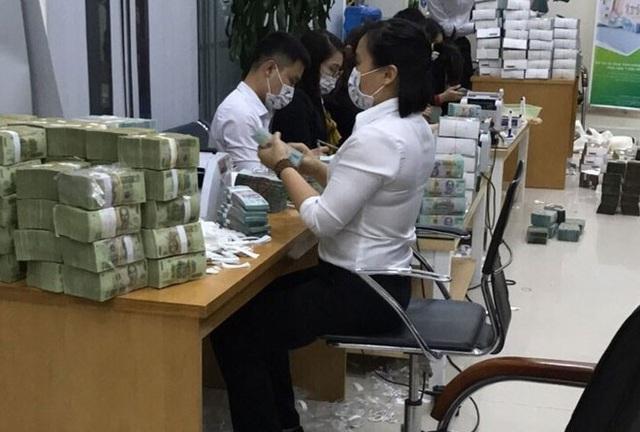 Nhân viên kiểm đếm số tiền tang vật của vụ án. Ảnh: CAND