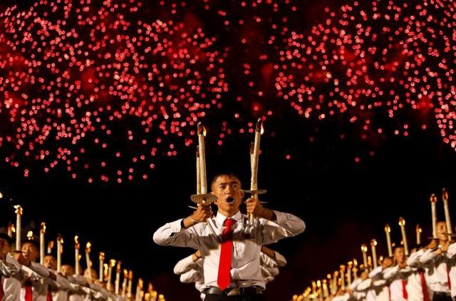 """Triều Tiên đã bắn pháo hoa để tạo thêm hiệu ứng cho màn đồng diễn tại quảng trường Kim Nhật Thành. Khi pháo hoa rực sáng trên trời, những người đồng diễn đã hát: """"Hãy bảo vệ Chủ tịch Kim Jong un bằng cuộc sống của chúng ta""""."""