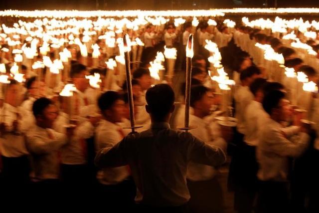 Những người tham gia đồng diễn phải nâng tay lên một góc 90 độ, di chuyển nhanh chóng giữa các vị trí để tạo thành các câu khẩu hiệu hoặc tạo hình.