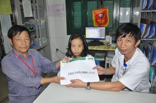 Anh Nguyễn Xuân Vinh - Điều dưỡng trưởng khoa Tim mạch, lồng ngực bệnh viện Việt Đức trao quà của bạn đọc Dân trí đến hai bố con.