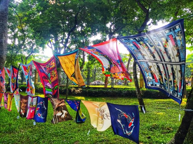 Hàng trăm chiếc khăn lụa mềm mại tung bay trong gió dưới những hàng cây cổ thụ mướt xanh.