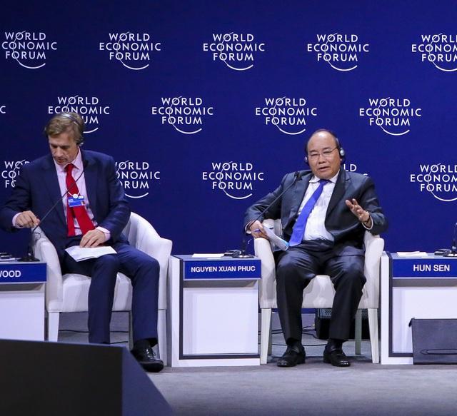 Thủ tướng Nguyễn Xuân Phúc (phải) trao đổi tại phiên thảo luận
