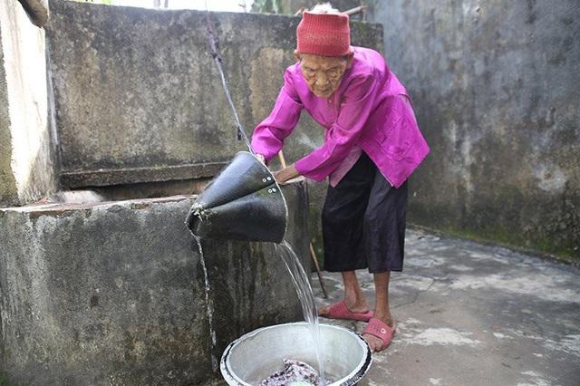 Cụ Thoại múc nước làm việc nhà.