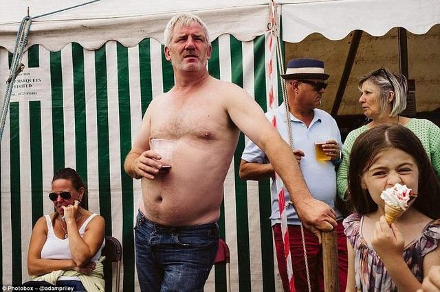 Một người đàn ông cởi trần đang cầm cốc nước uống dở trong khi bé gái say mê ăn kem.