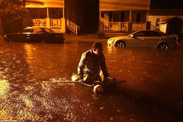 Người dân di chuyển khó khăn treen những con đường bị ngập sâu.