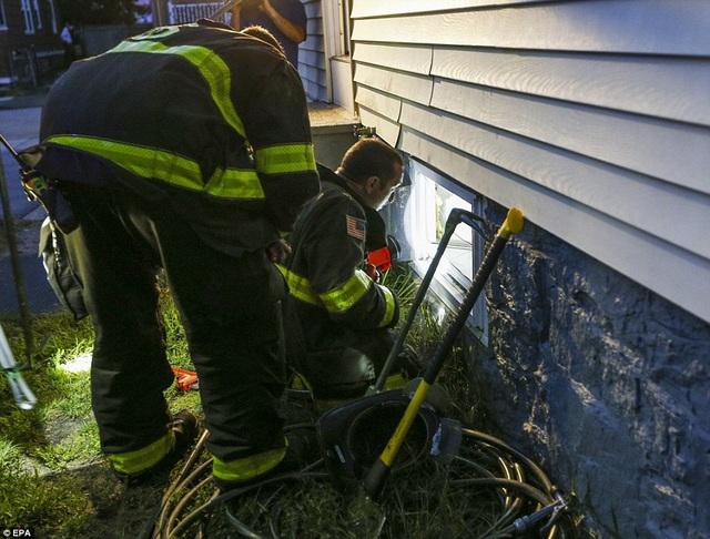 Các nhân viên cứu hỏa tìm cách vào một ngôi nhà thông qua tầng hầm để kiểm tra đường ống gas tại thị trấn Lawrence.