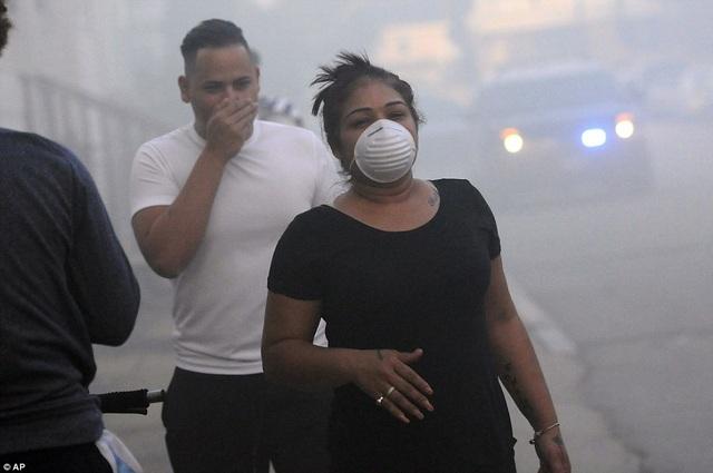 Người dân đeo khẩu trang và bịt miệng trong khi sơ tán khỏi hiện trường một vụ cháy trên phố Bowdoin, Lawrence.