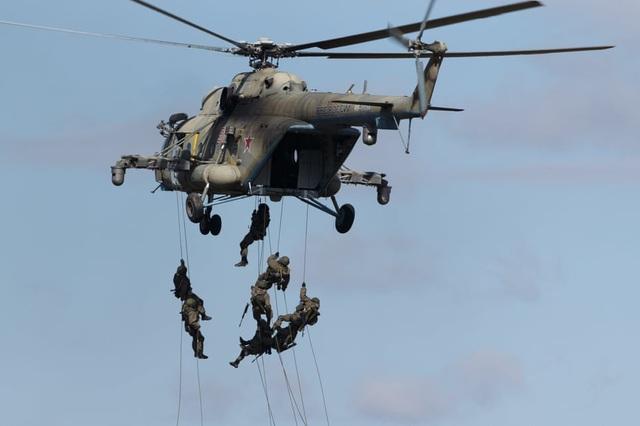 Các binh sĩ tập trận cùng trực thăng quân sự đa năng Mil Mi-8AMTSh-V. (Ảnh: TASS)