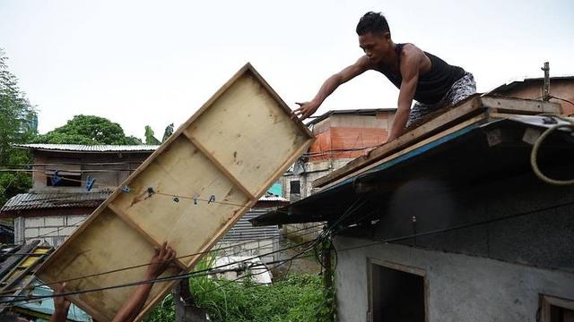 Với lượng mưa lớn, siêu bão Mangkhut được dự đoán sẽ gây ra tình trạng lũ lụt và sạt lở đất cho nhiều khu vực ở Philippines. Người dân ở nhiều nơi đã gia cố nhà cửa, đưa tàu thuyền lên bờ và chuẩn bị các điều kiện cần thiết đón siêu bão. (Ảnh: AFP)