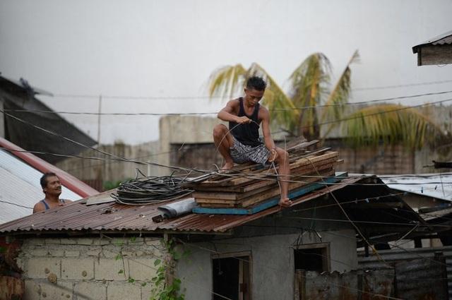 Ở khu vực phía bắc Philippines, người dân đã dùng các thanh gỗ để gia cố các cửa sổ bằng kính, đồng thời dùng dây thừng để cố định mái nhà, tránh trường hợp bị gió thổi bay. (Ảnh: AFP)