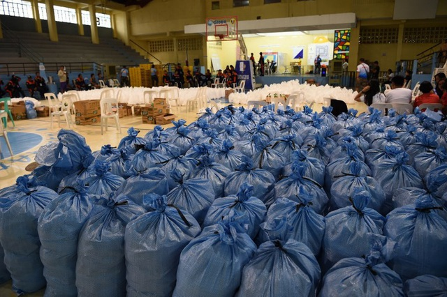 Ít nhất 135 chuyến bay đã bị hủy trên cả nước Philippines. Lực lượng tuần duyên Philippines cho biết hơn 4.000 người vẫn đang bị mắc kẹt trên các đảo vì phà không thể di chuyển do điều kiện thời tiết xấu. Trong ảnh: Các bao chứa lương thực được chuẩn bị cho người dân ứng phó với bão tại Philippines. (Ảnh: AFP)