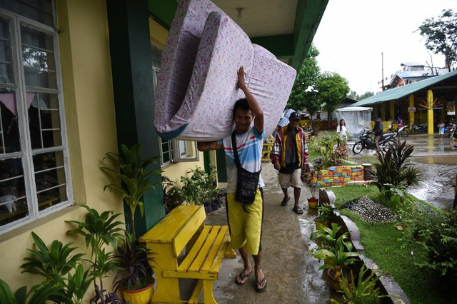 """""""Chính quyền đã nói rằng cơn bão này mạnh gấp 2 lần so với cơn bão trước, vì thế chúng tôi rất lo sợ. Chúng tôi đã học được bài học từ cơn bão gần đây nhất. Khi đó nước ngập lên cả mái nhà của chúng tôi"""", Myrna Parallag, 53 tuổi, nói sau khi sơ tán khỏi khu vực phía bắc Philippines. (Ảnh: AFP)"""