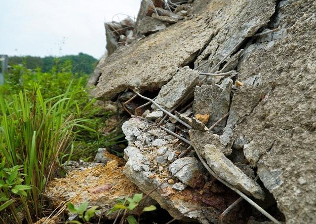 Bờ taluy tại km163 được chủ đầu tư thiết kế xây dựng chắc chắn bằng bê tông cốt thép. Tuy nhiên, theo ghi nhận của PV Dân trí, hàng trăm mét bờ kè bằng bê tông kiên cố bị vỡ vụn, trơ lõi thép, đất đá tràn xuống rào tôn hộ lan.