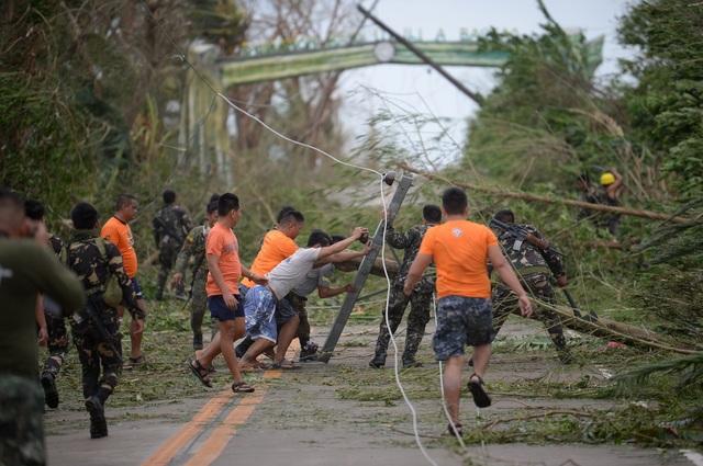 Theo New York Times, sau 12 giờ bão Mangkhut đổ bộ vào Philippines, hiện đã có một trường hợp được ghi nhận là thiệt mạng. Giới chức Philippines vẫn chưa bắt đầu đánh giá thiệt hại do bão gây ra. Trong ảnh: Các nhân viên cứu hộ dựng lại các cây và cột điện bị đổ khi bão Mangkhut càn quét khu vực Baggao thuộc tỉnh Cagayan, phía bắc thủ đô Manila, Philippines sáng 15/9. (Ảnh: AFP)
