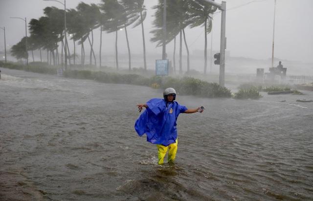 Philippines đã huy động đông đảo các binh sĩ, cảnh sát và các đội cứu hộ để giúp người dân sơ tán và khắc phục hậu quả do bão Mangkhut gây ra. Trong ảnh: Cảnh sát giao thông hướng dẫn các phương tiện di chuyển trên đường ngập nước ở thủ đô Manila, Philippines. (Ảnh: Bloomberg)