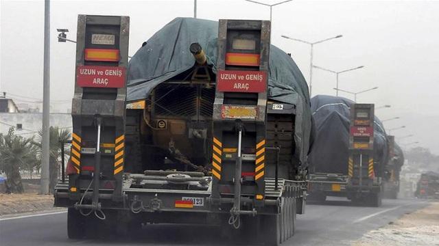 Xe tải chở xe tăng Thổ Nhĩ Kỳ tiến gần biên giới Syria (Ảnh: Aljazeera)