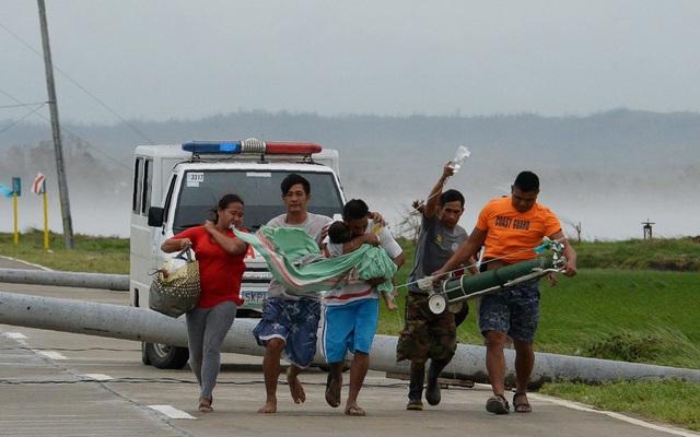 Bão Mangkhut đã phá hủy một sân bay và nhiều đoạn đường đóng vai trò quan trọng trong việc vận chuyển hàng cứu trợ tại Philippines. Trong ảnh: Một người cha ôm con trai bị ốm từ xe cấp cứu sang một xe khác sau khi xe cấp cứu bị cột điện đổ chắn ngang đường do gió lớn tại tỉnh Cagayan. (Ảnh: AFP)