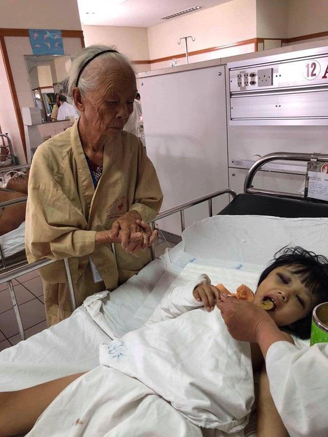 Bé Thu Trâm được cụ Cẩm 78 tuổi chăm sóc trong bệnh viện. Ảnh:Uyển Hương