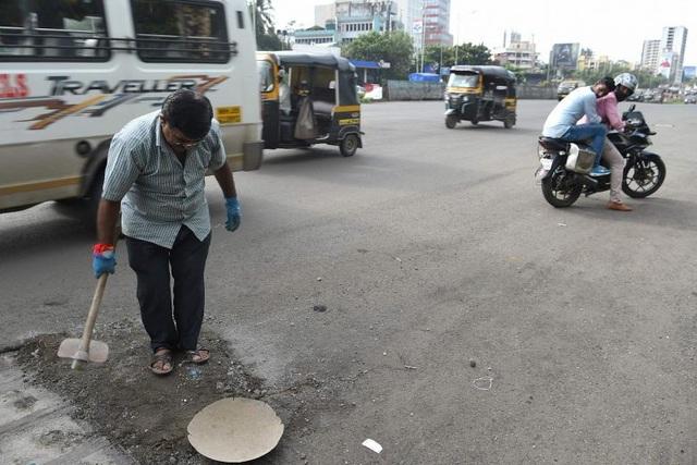 Ông Dadarao Bilhore lấp một ổ gà trên đường cao tốc Western Express ở Mumbai, Ấn Độ, ngày 29.8. Ảnh: AFP