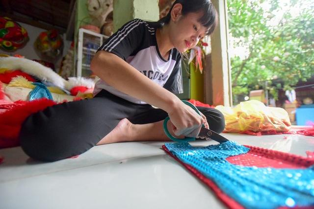 Trang trí đầu lân đòi hỏi sự công phu, cắt tỉa từng miếng vải miếng lông cừu để gắn vào.
