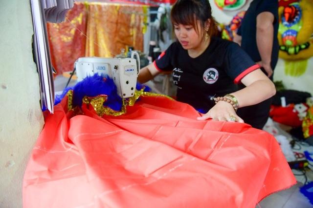 Nhiều năm đồng hành cùng chồng, chị Nguyễn Thị Mẫn (28 tuổi, vợ anh Tưởng) thấu hiểu sự vất vả của nghề. Chị đảm nhận việc cắt kim sa, vải làm thân, rồi may vảy, quần cho lân, rồng.