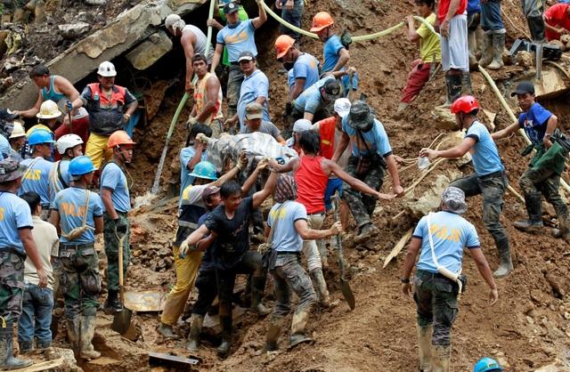 Do đất ngấm nước bị nhão nên lực lượng cứu hộ không thể sử dụng các máy móc hạng nặng để tìm kiếm các thi thể bị vùi lấp. Họ phải sử dụng xẻng và dùng tay không để cào đất trong quá trình tìm kiếm các nạn nhân. (Ảnh: Reuters)