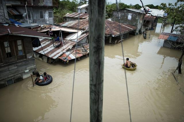 Chỉ tính riêng tại tỉnh Benguet đã có ít nhất 32 người chết và 29 người mất tích, phần lớn ở những khu vực xảy ra sạt lở đất khi mưa lớn ập xuống. Trong ảnh: Trẻ em dùng các vật dụng để làm phương tiện di chuyển do ngập lụt ở Philippines. (Ảnh: AFP)