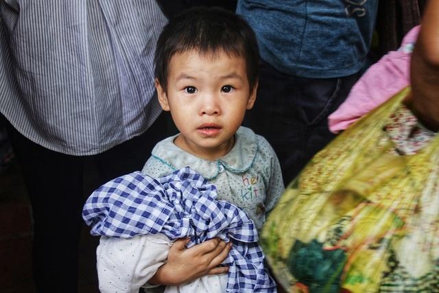 Các em nhỏ đi theo bà; mẹ, lọt thỏm trong đám đông người lớn, chờ đợi để được mặc bộ quần áo mới.