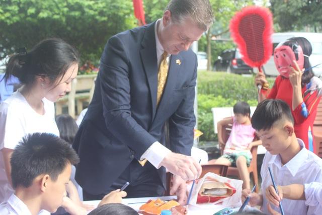 Nhà ngoại giao Mỹ vừa trang trí mặt nạ, vừa trò chuyện với các em nhỏ Việt Nam.