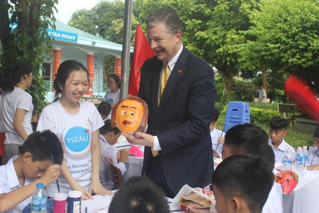 Đại sứ Kritenbrin vui vẻ chia sẻ với các em nhỏ chiếc mặt nạ do ông tự tay vẽ.