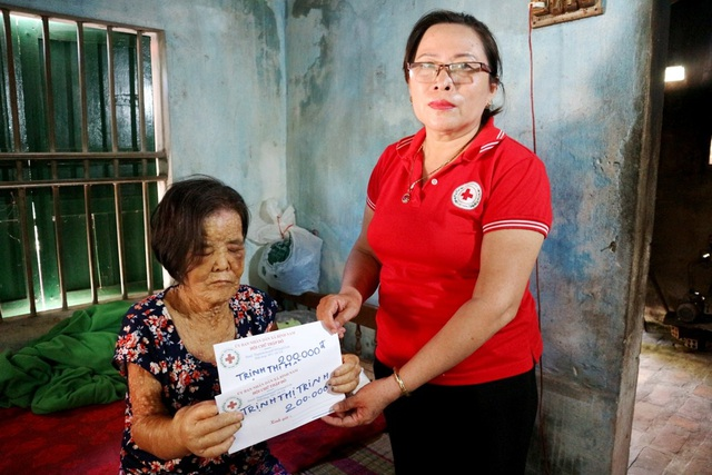Đại diện Hội chữ thập đỏ xã Bình Nam trao tiền ủng hộ 400 ngàn đồng của các mạnh thường quân để giúp đỡ thêm cho gia đình bà Quân