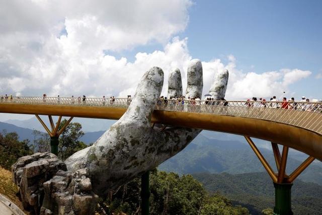 Các du khách đi qua biểu tượng bàn tay khổng lồ trên Cầu Vàng trên đỉnh Bà Nà, Đà Nẵng. Cây cầu này đã trở thành một trong những điểm đến yêu thích của du khách tại Đà Nẵng và xuất hiện nhiều trên báo chí quốc tế kể từ khi được khánh thành hồi tháng 6 năm nay.
