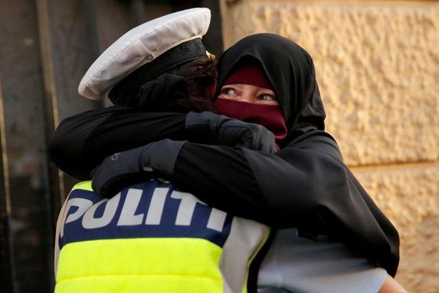 Ayah, 37 tuổi, ôm một sĩ quan cảnh sát trong cuộc biểu tình phản đối lệnh cấm đeo bịt mặt tại Copenhagen, Đan Mạch.