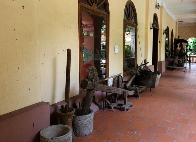 Dọc hành lang nhà truyền thống trưng bày nhiều vật dụng của nông dân Việt Nam cách đây hàng trăm năm như xe ngựa, guồng nước, cối giã gạo, cày, bừa...