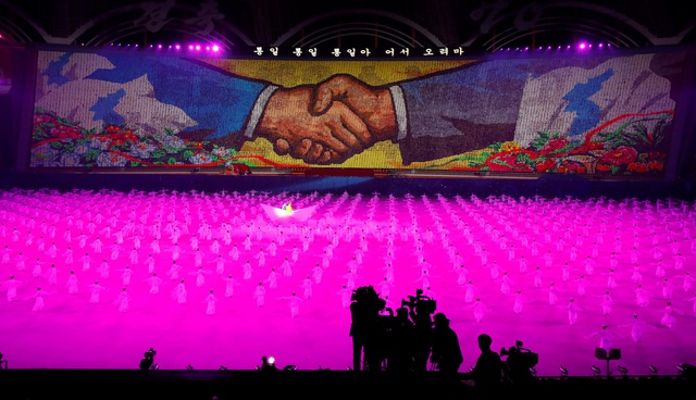 """Chương trình nghệ thuật đồng diễn của Triều Tiên mang tên """"Đất nước Vinh quang"""" với sự tham gia của hàng nghìn người. Hình ảnh hai bàn tay nắm chặt và bản đồ bán đảo Triều Tiên thống nhất do người Triều Tiên xếp lại từ các tấm bảng cho thấy thông điệp hợp tác và hòa bình của Bình Nhưỡng."""