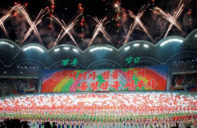 Hàng nghìn người đã ngồi trên khu vực ghế dành cho khán giả tại sân vận động 1/5 và cầm các bảng màu để xếp thành các bức hình hoặc khẩu hiệu khổng lồ.