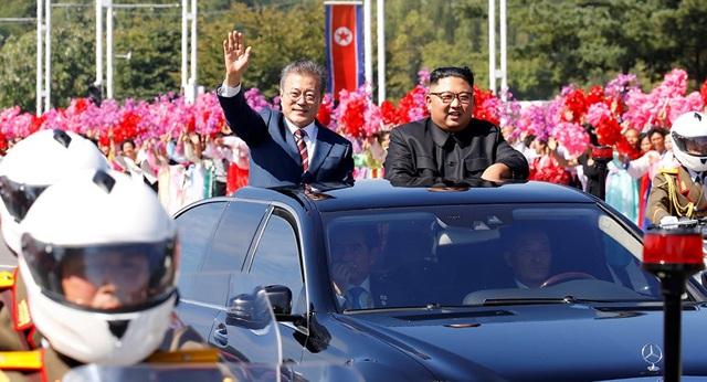 Người dân Triều Tiên đứng hai bên đường vẫy tay chào đón Tổng thống Moon Jae-in và nhà lãnh đạo Kim Jong-un (Ảnh: Reuters)