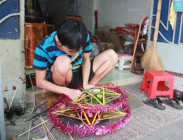 Anh Nguyễn Trọng Hiệp, em của anh Nguyễn Trọng Thành, dán lại chiếc đèn lồng để giao hàng cho khách hàng.