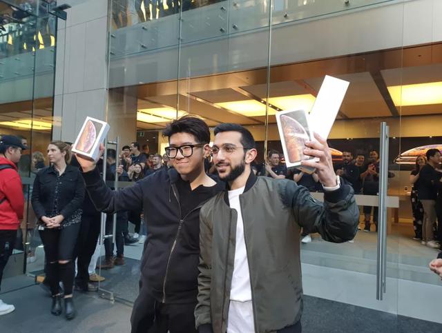 Tuy nhiên danh hiệu số 1 thế giới lại thuộc về Teddy Lee (trái), một sinh viên tới từ Hàn Quốc sau khi đứng xếp hàng từ 6 giờ sáng tại Apple Store ở Sydney, Australia. Như mọi năm thì Australia vẫn luôn là nơi đầu tiên trên thế giới mở bán iPhone do chênh lệch múi giờ.