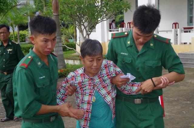 Các chiến sĩ bộ đội biên phòng giúp đỡ người bệnh đến nơi khám bệnh và nhận quà